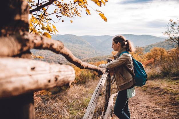 Mulher na montanha em pé ao lado da cerca e apreciando a vista Foto Premium