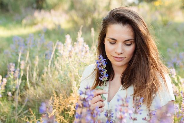 Mulher na natureza posando ao lado de lindas flores Foto gratuita