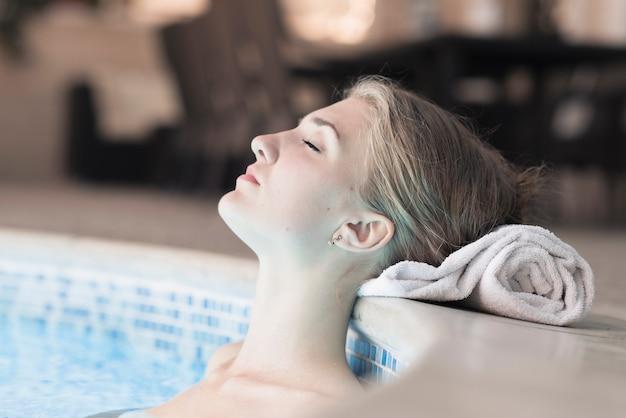 Mulher na piscina inclinando a cabeça na borda da toalha enrolada Foto gratuita