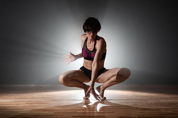 Mulher na pista de dança. dançarina feminina dançando em um fundo preto Foto Premium