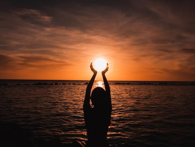 Mulher na praia com as mãos levantadas Foto Premium