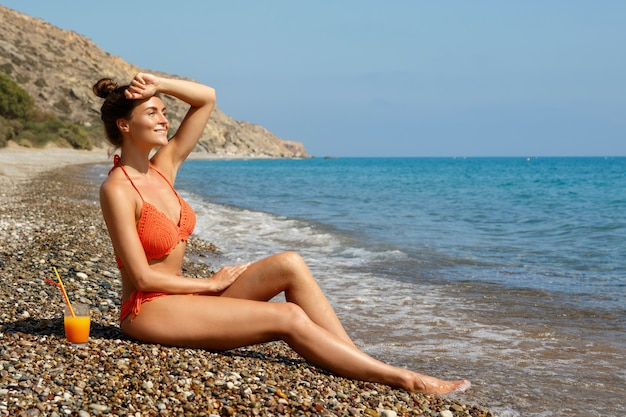 Mulher na praia com um copo de cocktail Foto Premium