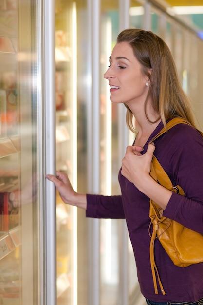 Mulher na seção de freezer de supermercado Foto Premium