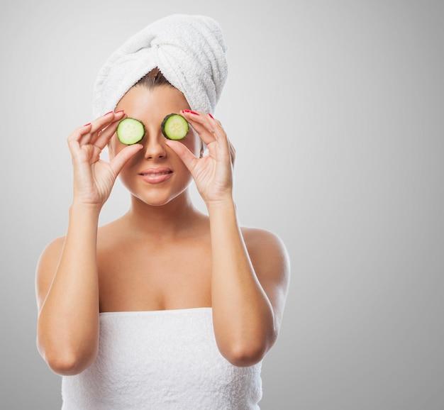 Mulher na toalha de sorriso com o pepino nos olhos Foto gratuita