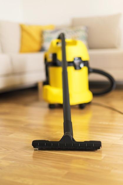 Mulher nas luvas protetoras que limpam a sala de visitas com o aspirador de p30 amarelo. conceito limpo Foto Premium