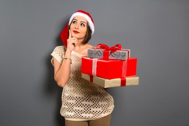 Mulher natal, olhar para cima cópia espaço vazio segurar caixa de presente presente, jovem sorriso feliz, usar chapéu de papai noel, garota atraente festeira de ano novo, Foto Premium