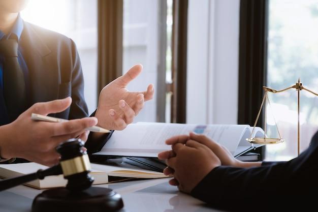 Mulher negócio, e, advogados, discutir, contrato, papeis, com, bronze, escala, ligado, escrivaninha madeira Foto Premium