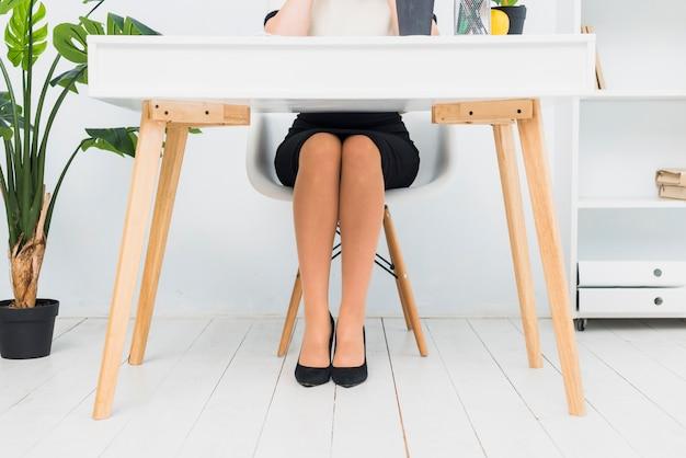 Mulher negócio, em, saia, sentando tabela Foto gratuita