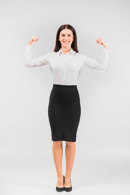 Mulher negócio, mostrando, braço, músculos Foto gratuita