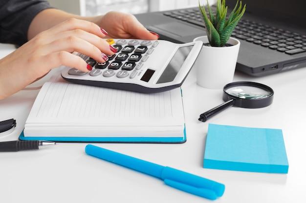 Mulher negócio, trabalhando, com, dados financeiros, mão, usando, calculadora Foto Premium