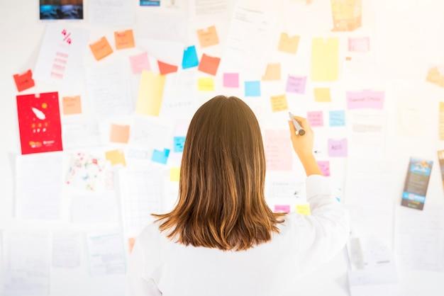 Mulher negócio, trabalhando, com, notas, em, um, escritório Foto gratuita