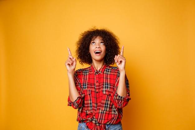 Mulher negra americana alegre na camisa vermelha que olha para cima e que aponta os dedos acima no espaço da cópia isolado sobre o fundo alaranjado. Foto gratuita