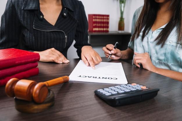Mulher negra, apontando para o documento perto de senhora com caneta na mesa com calculadora e martelo Foto gratuita