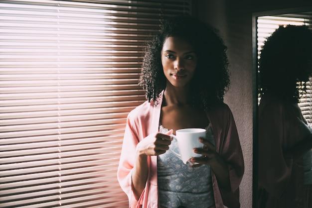 Mulher negra bonita em pé na janela com uma xícara de café Foto Premium