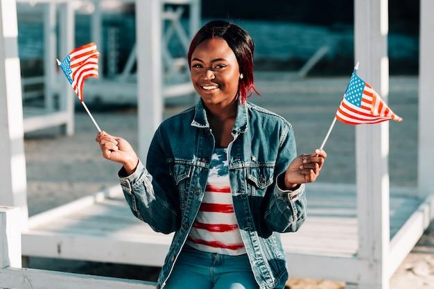 Mulher negra com bandeiras americanas sentado na praia Foto gratuita