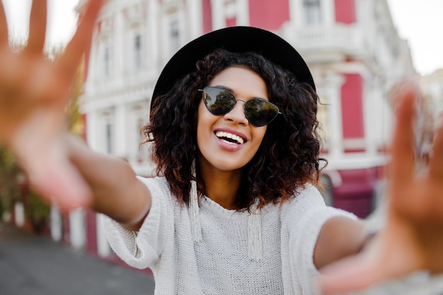 Mulher negra com cabelos afro elegantes, fazendo o auto-retrato. usando óculos escuros, chapéu preto e brincos elegantes. emoções felizes. fundo da cidade americana. Foto gratuita