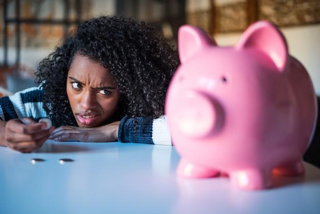 Mulher negra confusa pensativa com mealheiro Foto Premium