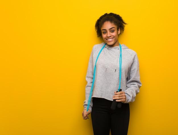 Mulher negra da aptidão nova alegre com um sorriso grande. segurando uma corda de pular. Foto Premium