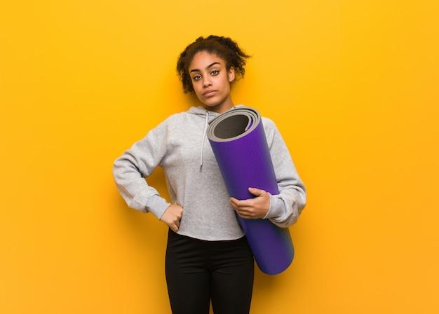 Mulher negra da aptidão nova que olha a direito. segurando um tapete. Foto Premium