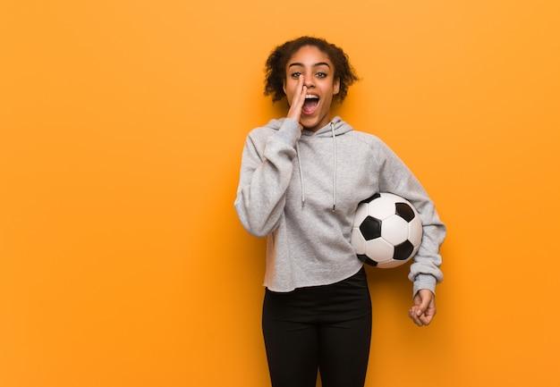 Mulher negra de aptidão jovem gritando algo feliz para a frente. segurando uma bola de futebol. Foto Premium