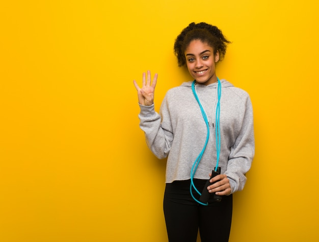 Mulher negra de aptidão jovem mostrando o número quatro. segurando uma corda de pular. Foto Premium