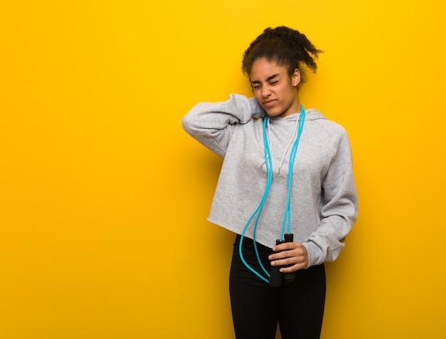 Mulher negra de aptidão jovem que sofre de dor de garganta. segurando uma corda de pular. Foto Premium