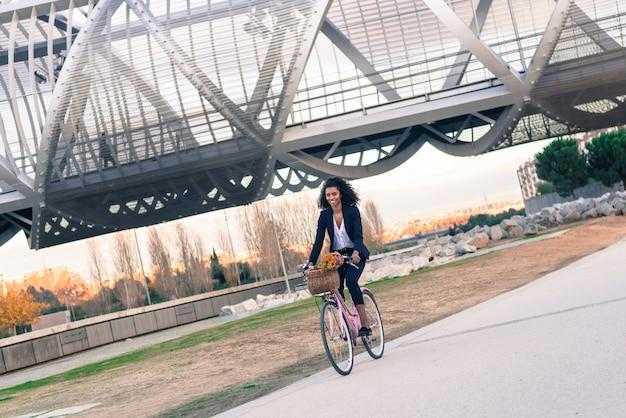 Mulher negra de negócios andando de bicicleta vintage na cidade Foto Premium