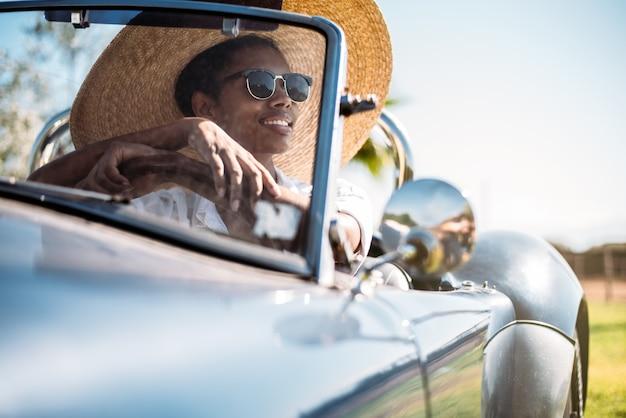 Mulher negra, dirigindo um carro conversível antigo Foto Premium