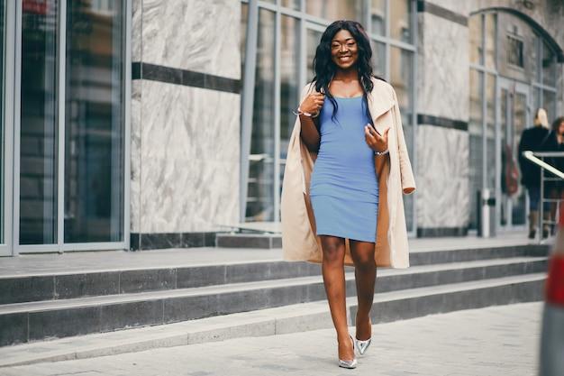 Mulher negra em pé em uma cidade de outono Foto gratuita