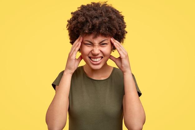 Mulher negra franze a testa em desgosto, cerra os dentes, mantém as mãos nas têmporas Foto gratuita
