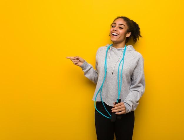 Mulher negra jovem aptidão apontando para o lado com o dedo. segurando uma corda de pular. Foto Premium