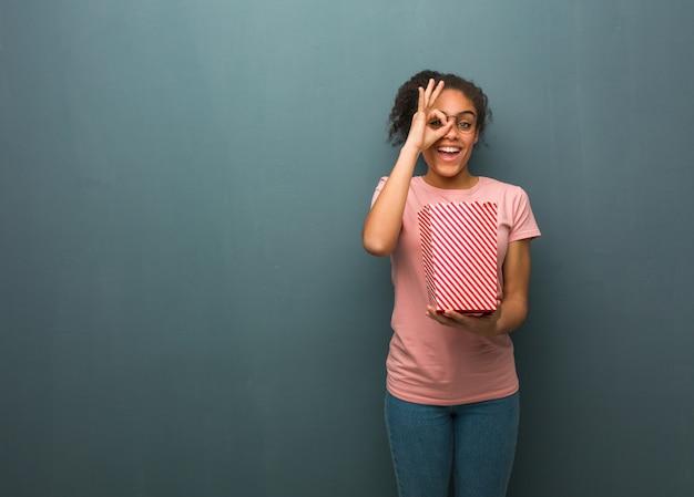 Mulher negra nova confiável fazendo o gesto aprovado no olho. ela está segurando um balde de pipoca. Foto Premium