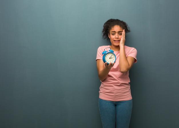 Mulher negra nova desesperada e triste. ela está segurando um despertador. Foto Premium