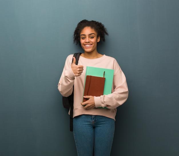 Mulher negra nova do estudante que sorri e que levanta o polegar acima. ela está segurando livros. Foto Premium