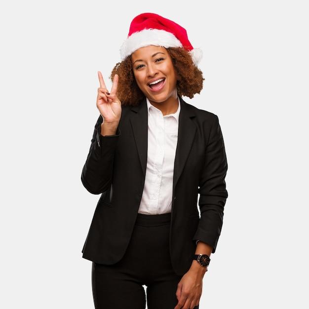 Mulher negra nova do negócio que veste um divertimento do chapéu do papai noel dos chirstmas e feliz fazendo um gesto da vitória Foto Premium
