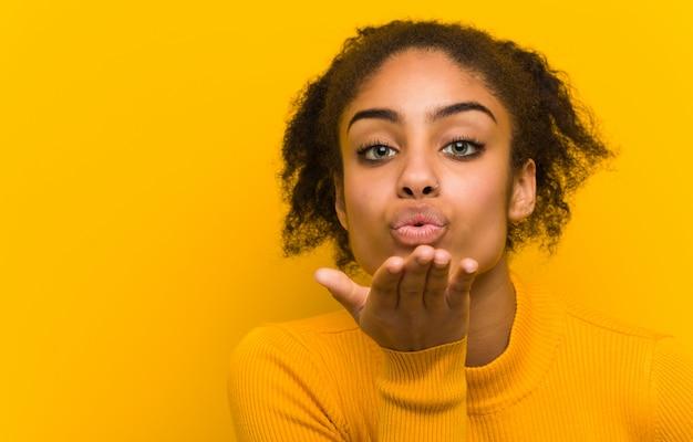 Mulher negra nova que envia um beijo, parede alaranjada. Foto Premium