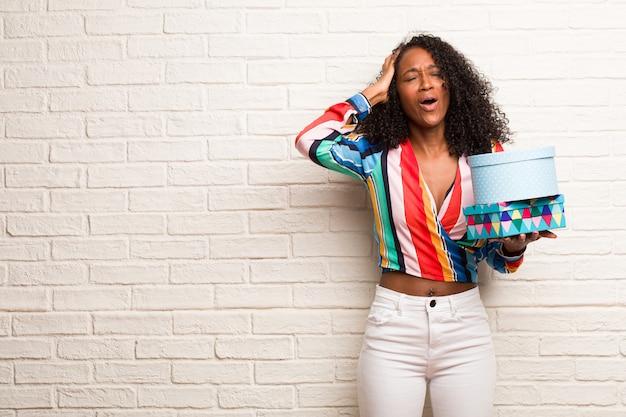 Mulher negra nova que escuta a música, dançando e se divertindo, movendo-se, gritando e expressando a felicidade, conceito da liberdade Foto Premium