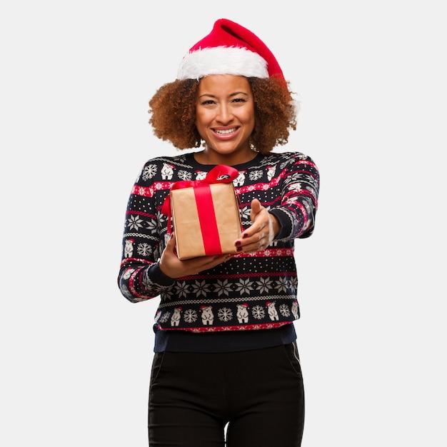 Mulher negra nova que guarda um presente no dia de natal que alcança para fora para cumprimentar alguém Foto Premium