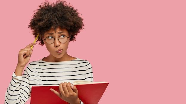 Mulher negra perplexa tem expressão contemplativa, escreve para fazer lista de metas, segura caderno, coça a cabeça com lápis Foto gratuita