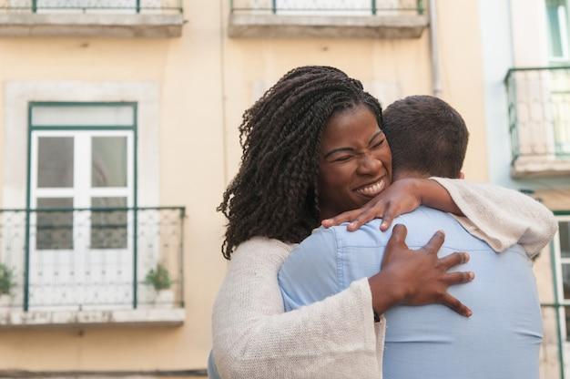 Mulher negra positiva abraçando o namorado ao ar livre Foto gratuita