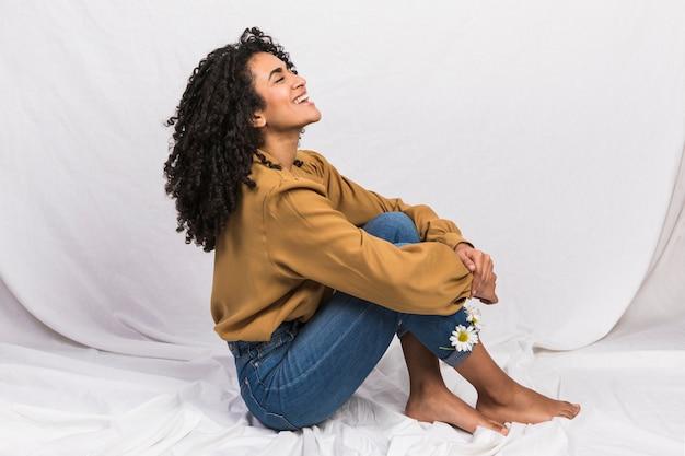 Mulher negra sentada com margarida flores em punhos de jeans Foto Premium
