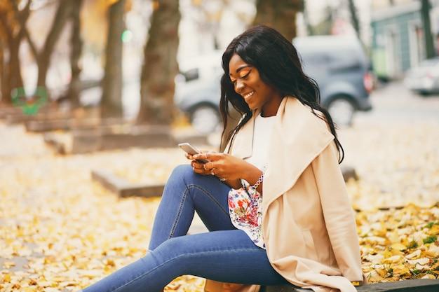 Mulher negra sentada em uma cidade de outono Foto gratuita