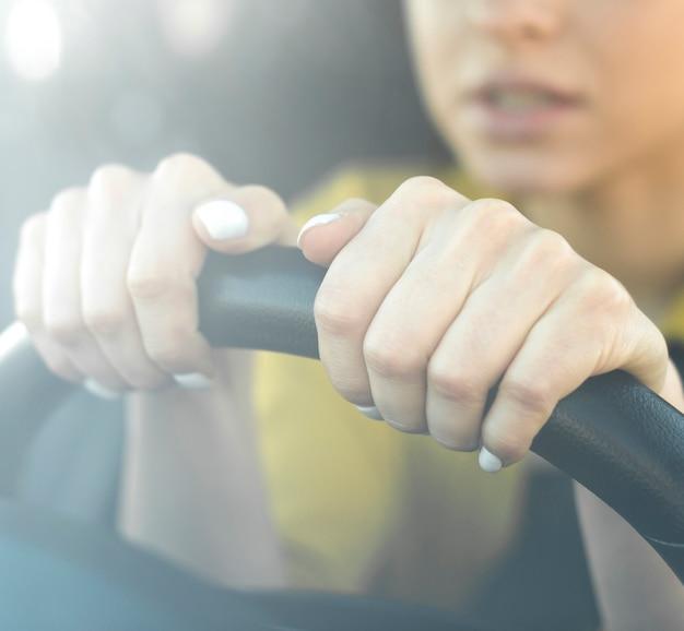 Mulher nervosa de close-up, segurando o volante Foto gratuita