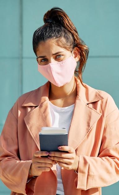 Mulher no aeroporto durante pandemia com máscara médica e passaporte Foto gratuita