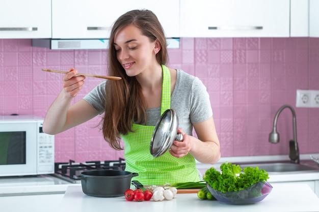 Mulher no avental que prova pratos dos vegetais maduros em casa. alimentos limpos e nutrição adequada. estilo de vida saudável, dieta. preparação de cozinha para o almoço Foto Premium