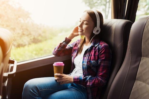 Mulher no banco do passageiro do ônibus ouve música Foto Premium
