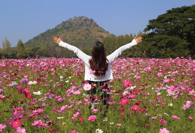 Mulher no campo de flor do cosmos | Foto Premium