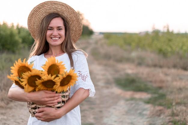 Mulher no campo segurando a vista frontal dos girassóis Foto Premium