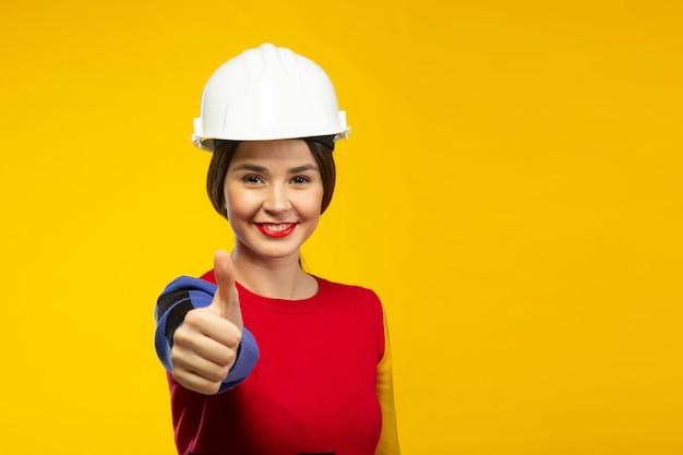Mulher no capacete de construção mostra os polegares Foto gratuita