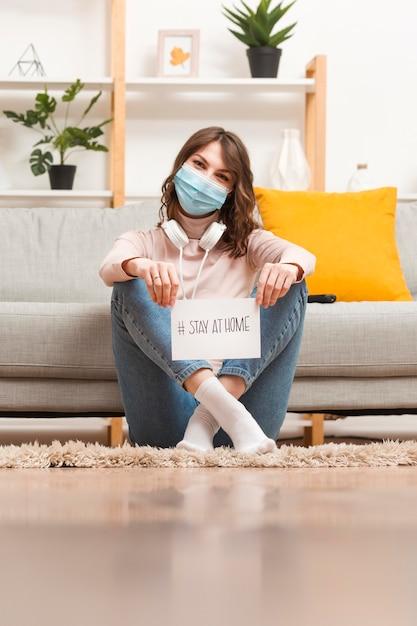 Mulher no chão com a mensagem de ficar em casa Foto gratuita